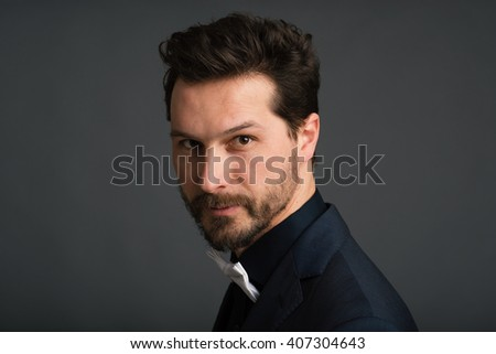 Elegant hipster man close up portrait against dark background.
