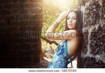 Elegant lady outdoors near the old stony walls. Sunlight at the background