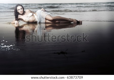 Elegant lady with perfect body laying at the beach. Evening photo during sunset. Natural colors and darkness