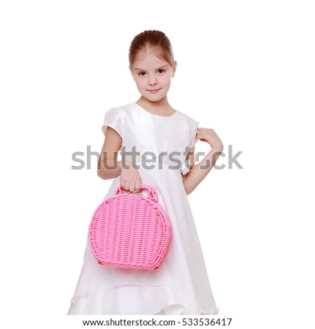 Elegant little girl in a white dress holding a pink basket