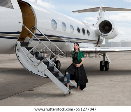 Elegant pretty young woman boarding a private jet