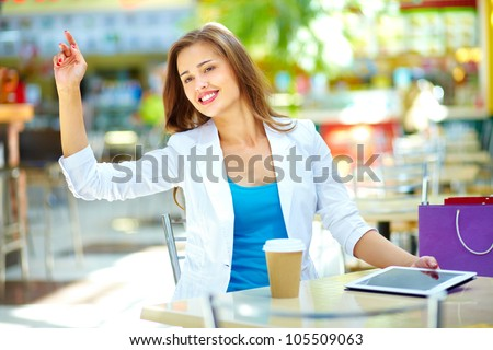 Elegant woman sitting at table asking for the bill by gesture