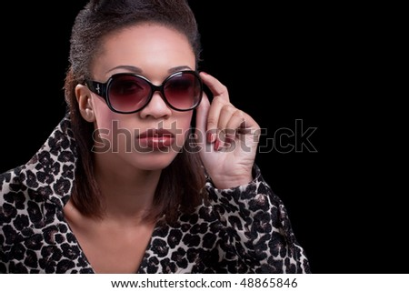 Elegant woman wearing dark sunglasses and an animal print jacket, isolated over black
