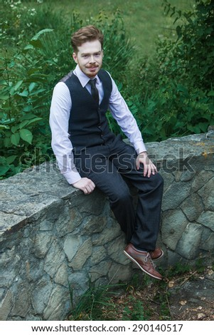 Elegant young handsome man in classic costume in city park.Fashion portrait of young  man in classic costume.Business men in class costume
