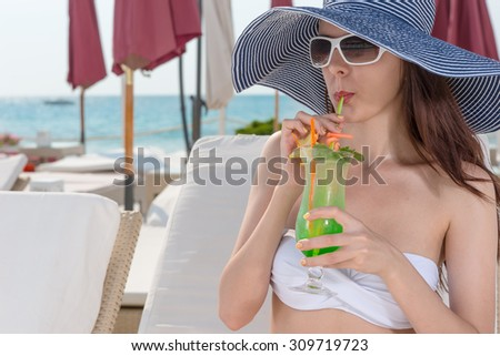 Elegant young woman in a straw sunhat and sunglasses sipping a tropical cocktail as she relaxes on a recliner chair at a seaside resort