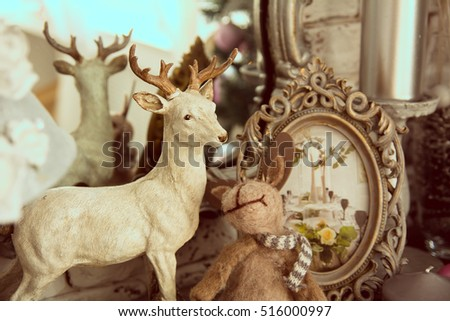 Element shelf with a mirror and standing deer and hare and frame with photos in retro style