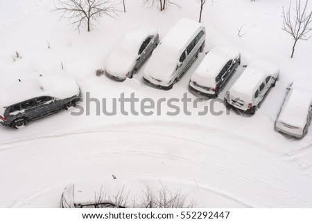 elevated view of new fresh snow covered cars in parking lot. top view