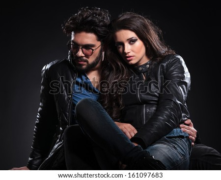 embraced seated couple in leather jackets pose on a dark studio background