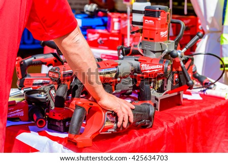 Emmaboda, Sweden - May 13, 2016: Forest and tractor (Skog och traktor) fair. A hand resting on one of many Milwaukee tools on a table.