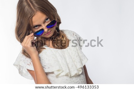Emotional blonde girl in a white dress with glasses on a white background