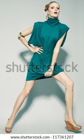 emotional gorgeous fashion model running in green (blue) dress over gray background. studio shot
