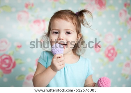 Emotional little girl playing with her knitted toys like sweet ice cream. Pastel colors. Floral background