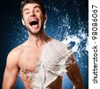 emotional man laughs. splashes of milk on his sexy body - stock photo