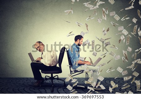 Employee compensation economy concept. Senior man working on laptop sitting next to young entrepreneur guy using computer under money rain. Pay difference concept.