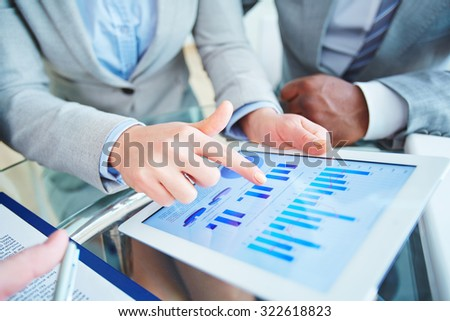 Employees with touchpad discussing marketing fluctuations