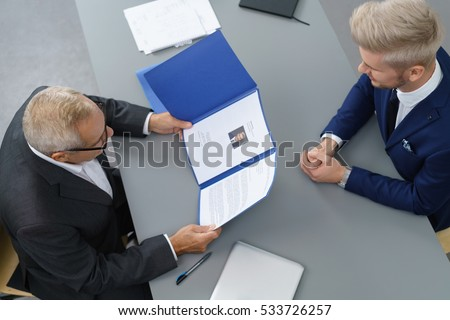 Employer interviewing a young male job seeker for a business vacancy sitting at a table reading his CV viewed from above