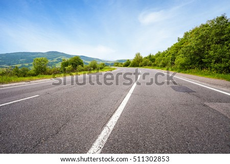 Empty asphalt road and summer landscape with green trees and remote mountains