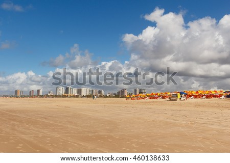 Empty beach Atalaia with chairs and umbrellas with view of city on background, Aracaju, Sergipe state, Brazil