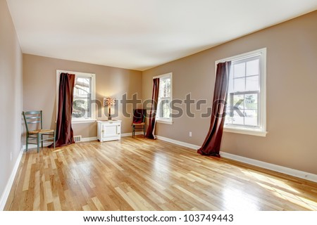Empty bedroom with three windows and hardwood floor.