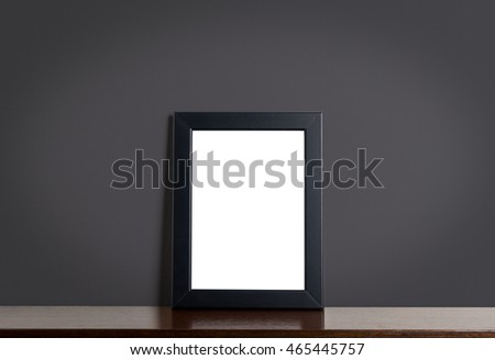 Empty Black photo frame on shelf with gray background.