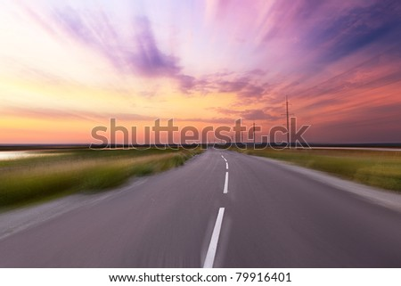 Empty blurry country road under sunset