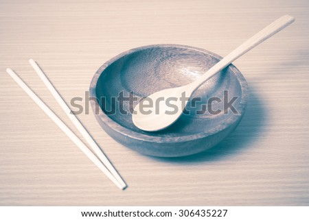 empty bowl with chopstick on wood table background vintage style