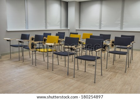 Empty bright lecture hall with chairs. Grey black yellow tones