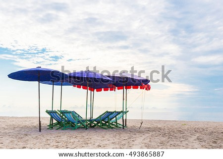 Empty chairs and sun umbrella on a sandy beach by the sea.