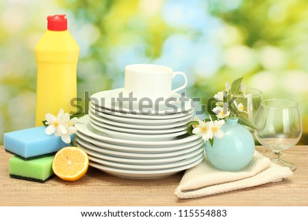 empty clean plates, glasses and cups with dishwashing liquid, sponges and lemon on wooden table on green background