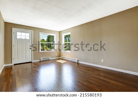 Empty house interior. Hardwood floor and beige walls. White entrance door and two windows in spacious room