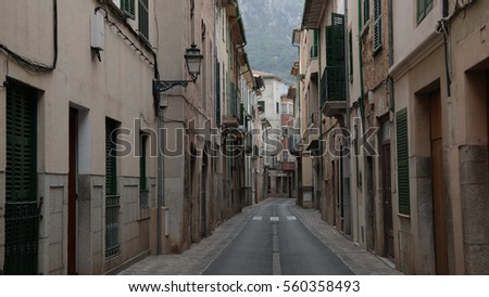 empty narrow street in Soller Majorca with typical historic houses on both sides and mountains in far distant background