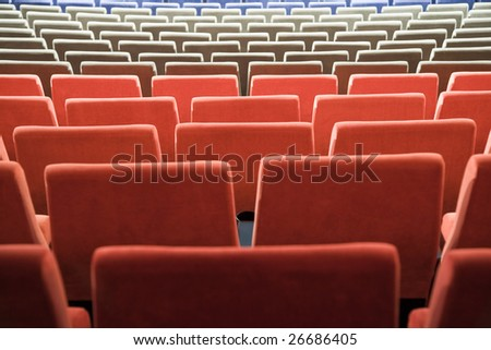Empty new cinema auditorium with rows of blue, gray and red chairs.