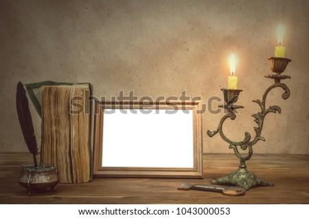 Empty Photo Frame With Copy Space, Book And Burning Candle In Vintage  Candlestick And Feather