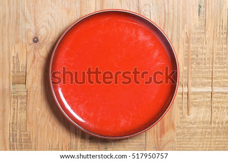 Empty red plate on old wooden background, top view