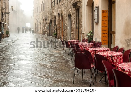 Empty restaurant chairs and tables in the street after rain, San Gimignano city in Tuscany, Italy.