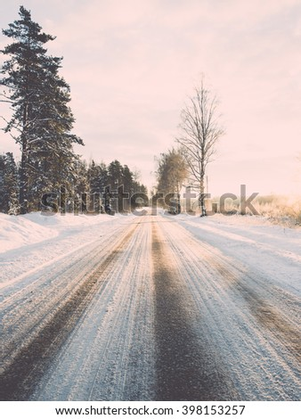 empty road in the countryside with trees in surrounding. perspective in winter - vintage film effect