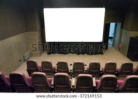 Empty stage in the small movie theater with white isolated screen