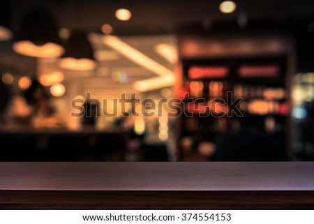 Empty top of wooden table or counter on cafeteria, bar, coffee shop background. For product display