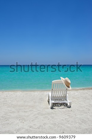 Empty tropical beach chair with hat  at shoreline in the Caribbean