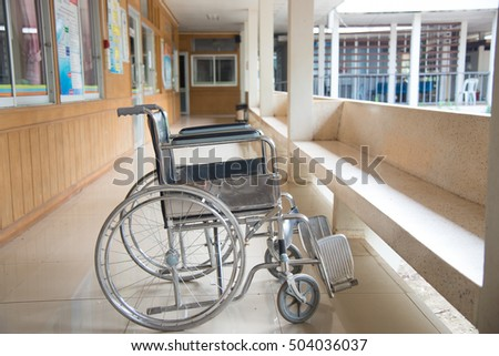 Empty wheelchair parked in hospital with selective focus.
