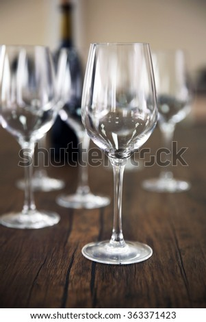 Empty Wine Glasses With Bottle On Wooden Table Against Blurred Background