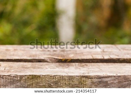 Empty wooden deck table with park background