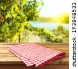 Empty wooden deck table with tablecloth over vineyard bokeh background - stock photo