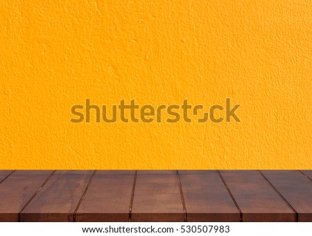 Empty wooden floor.Cement yellow wall background. There is an empty space for productions
