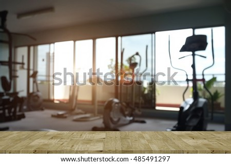 Empty wooden top table and fitness Gym blurred background. For product display.