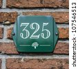 enameled house number three hundred and twenty-five atop a small tree symbol. White lettering on a green plate - stock photo
