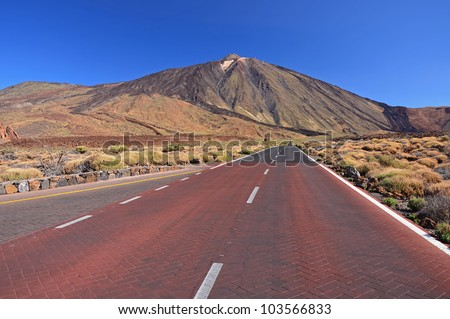 Endless mountain road with red colored asphalt in Teide National Park, Tenerife