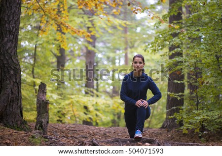 Energetic young woman do exercises outdoors in park to keep their bodies in shape.