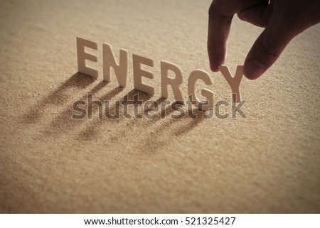 ENERGY wood word on compressed board,cork board with human's finger at Y letter