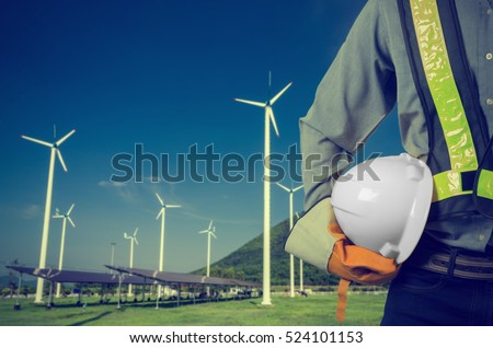 Engineer holding a whwite helmet. Against a backdrop of renewable energy farms. Vintage Style.